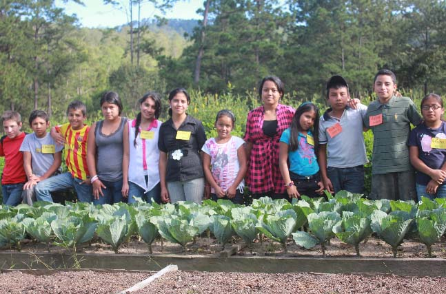 The next generation of COMSA innovators proudly display their organic, raised-bed vegetable gardens.