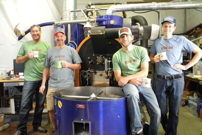"""Pictured here (from left to right), Sales Manager Mark Siegfried, Owner Glenn Lathrop, Production Assistant Ronnie Hardt and Roaster Zachary Ray.  """"The Desert Sun crew takes a break in front of """"Big Blue"""" their hard-working Diedrich 30 - the MACHINE that churns out their daily brew!"""